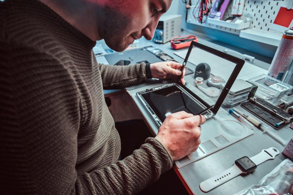 The technician repairs a broken tablet computer in a repair shop